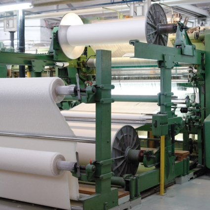 Gripper Loom at work: two loom beams of mohair each weighing 450-500 kg provide the warp and the pile of the three dimensional fabric which immediately after the weaving process is split into two